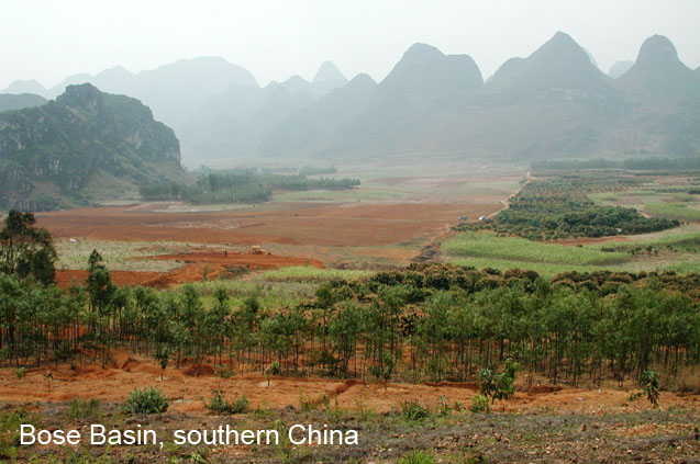 Landscape image of green crops and reddish, orange tilled soil in Bose Basin. In the misty distance are karst mountains.