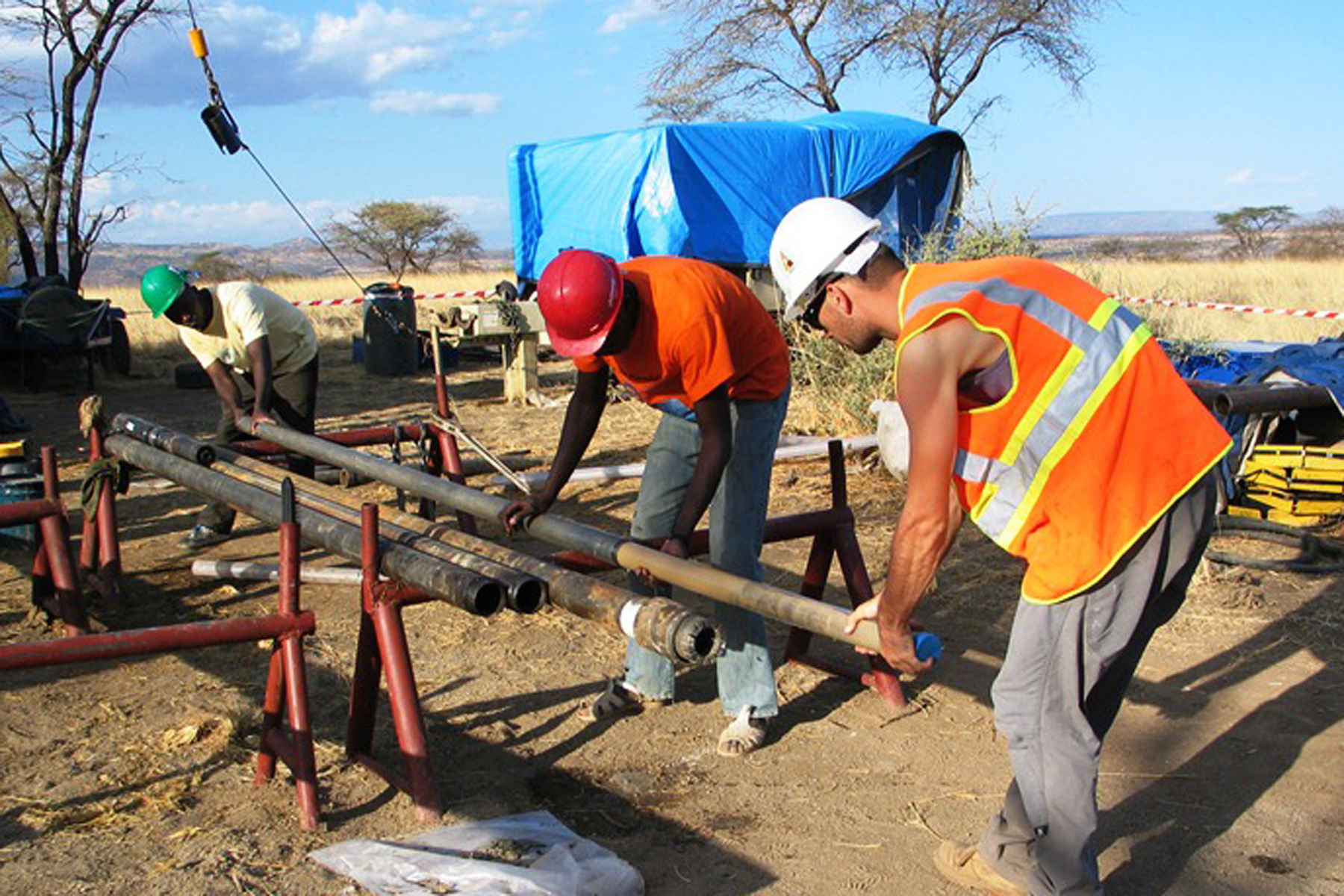 Two men wearing hard hat and safety vest pulling a long thin plastic tube of cored sediment from a metal casing