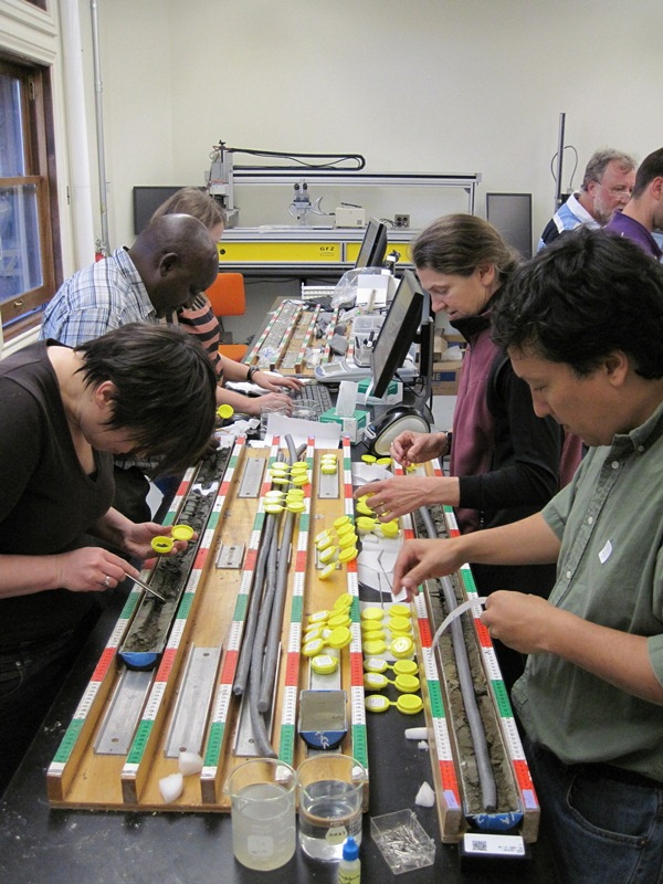 Four scientists crowd around a lab bench collecting samples from geological cores in long tubular trays.