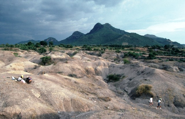 A small group of people huddle in a excavation pit in an expanse of barren grey/tan ground. In the background, stand sharp mountains covered in lush green vegetation.